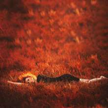 Girl Lying on Red Grass Field